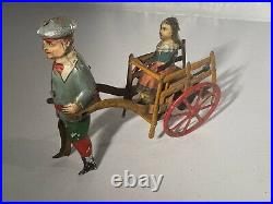 C. 1920 German Issmayer Tin windup Boy pulling Girl in Cart Tin Toy